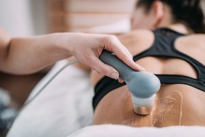 Ultrasound in Physical Therapy. Therapist Using Ultrasound Applicator on a Patient's Lower Back
